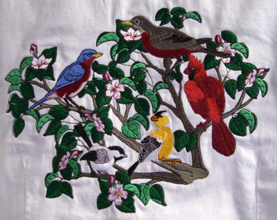 Embroidery of brids in a bush.
